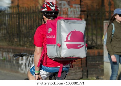 Berlin, Germany - April 8, 2018: Back turned Foodora delivery man at work on bike. Foodora GmbH is a Berlin-based online food delivery company