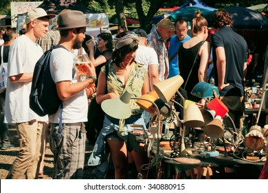 BERLIN, GERMANY - AUG 30, 2015:  Flea market with young people choosing vintage lamps and furniture on August 30, 2015. Urban area of Berlin comprised 4 million people, 7th most populous in EU