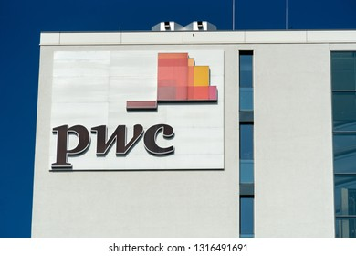 Berlin, Germany - August 15, 2018: PwC  sign outside a building. PricewaterhouseCoopers is a multinational professional services network, the second largest professional services firm in the world
