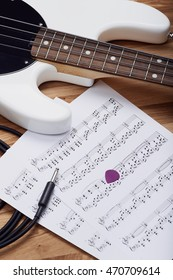 BERLIN, GERMANY - August 16, 2016: Illustrative editorial photo of a white Musicman bass guitar with sheet music on a wooden floor.