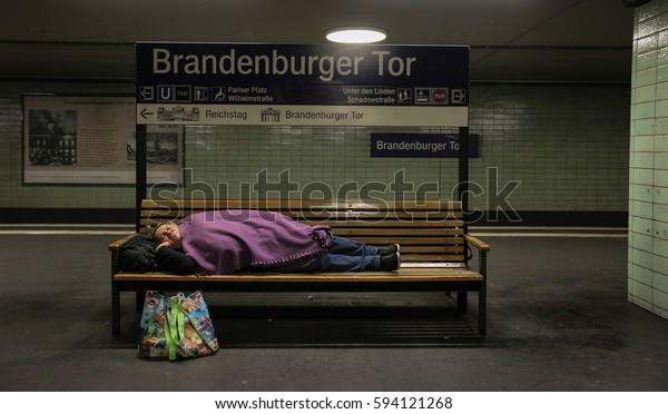 BERLIN, GERMANY - August 18, 2014: A passenger sleeps on a bench in the underground station near the Brandenburg Gate.