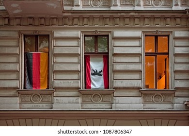 BERLIN / GERMANY - AUGUST 2008:  Three windows of tenement buildiing with German and Berlin flags hanging in the Windows