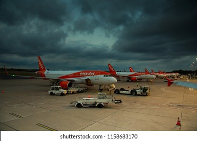 Berlin Germany - August 2018: several Easyjet Airbus A320 airplanes at Berlin Tegel (EDDT, TXL) airport during cloudy sunset