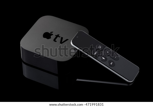 Berlin, Germany - August 21, 2016: Product shot of a fourth generation Apple TV and remote on black background.