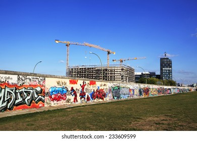 BERLIN, GERMANY - AUGUST, 26, 2013. Back site of the East Side Gallery wall of Berlin Germany, with a construction site on the background of the picture.
