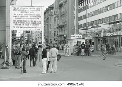 BERLIN, GERMANY - AUGUST 26, 2014: People visit famous Checkpoint Charlie in Berlin. During the Cold War it was the best known crossing of Berlin Wall.