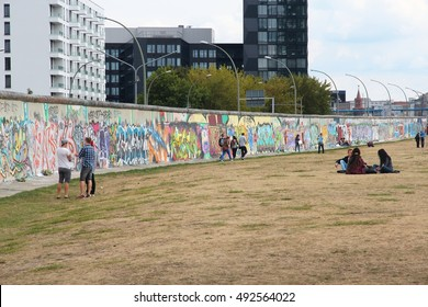 BERLIN, GERMANY - AUGUST 26, 2014: People visit the Berlin Wall (Berliner Mauer). Iconic iron curtain border divided Berlin in years 1961-1989.