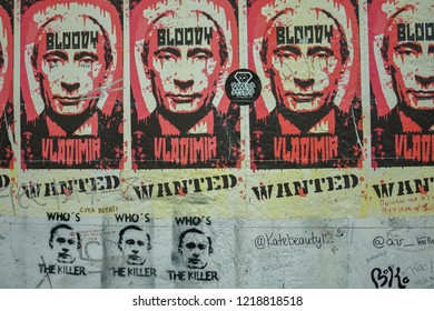 "Berlin / Germany - August 26 2018: posters of Russian President Vladimir Putin on the Berlin wall. Putin's face is shown dripping in blood with the caption ""bloody Vladimir""."