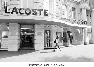 BERLIN, GERMANY - AUGUST 27, 2014: Person walks by Lacoste store at (Ku'Damm) Avenue in Berlin. There are more than 1100 Lacoste stores worldwide (2013).