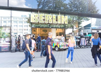 BERLIN, GERMANY -AUGUST 28, 2017; Curious tourists and passers-by on street in Alexandra Platz in front of shop with interesting object under big BERLIN sign.