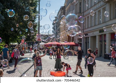 Berlin, Germany . August 29, 2017 : Girl making soap bubbles on a sunny day on the street in Berlin, Germany.