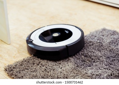 Berlin, Germany, August 29, 2019. irobot vacuum cleaner roomba cleaning a gray carpet. home cleaning concept.