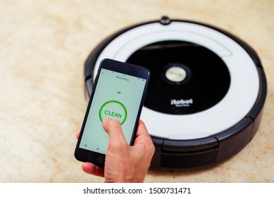 Berlin, Germany, August 29, 2019. Man hand activating the roomba irobot vacuum cleaner from the application. Smart life concept, smart city, smart home.