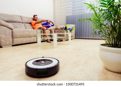 Berlin, Germany, August 29, 2019. irobot roomba cleaning the living room floor while two men are sitting on a sofa. Relaxing moment