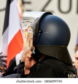 Berlin, Germany, August 29., 2020: Police officer protected by a helmet, in the background the war flag of the German Reich, a sign of the right-wing radicals
