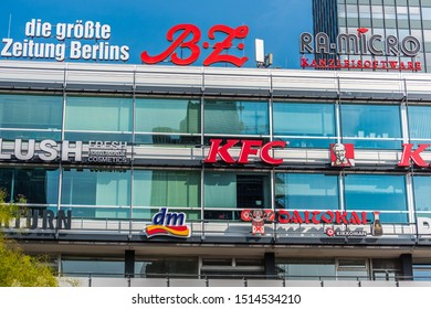 Berlin, Germany, August 29,2018, A modern shopping mall with lots of logos near A couple statue on the wall of Kaiser Wilhelm Memorial Church (Kaiser-Wilhelm-Gedächtniskirche)