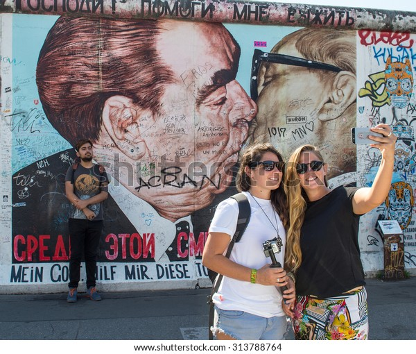 BERLIN, GERMANY - AUGUST 30, 2015: Young people taking selfie pictures on the famous Berlin Wall. Graffiti at the East Side Gallery in Berlin, Germany