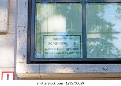 """BERLIN, GERMANY - August 6, 2018: Window on a wall. Sign translation: """"Military security area. Unauthorized trespassing is prohibited! Attention, use of firearms! Federal Minister of Defence"""""""