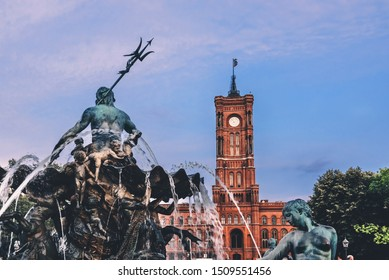 Berlin, Germany - August 7, 2018. Statues of Neptune Fountain aka Neptunbrunnen and Rotes Rathaus red brick building. Berlin City Hall and sculptures of Roman god of water and Prussia's main rivers.