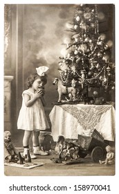 BERLIN, GERMANY - CIRCA 1900: antique photo of little girl with christmas tree and vintage toys, circa 1900 in Berlin, Germany