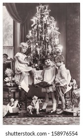 BERLIN, GERMANY - CIRCA 1900: antique photo of happy kids with christmas tree, gifts and vintage toys. vintage picture with film grain, circa 1900 in Berlin, Germany