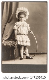 BERLIN, GERMANY - CIRCA 1900: old photo of little girl with toy wearing vintage dress. nostalgic picture, circa 1900 in Berlin, Germany