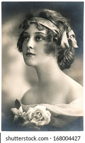 BERLIN, GERMANY - CIRCA 1918: Portrait of young woman with rose flower. Typical look for a woman of this period. art deco. Vintage photograph from circa 1918 in Berlin, Germany.