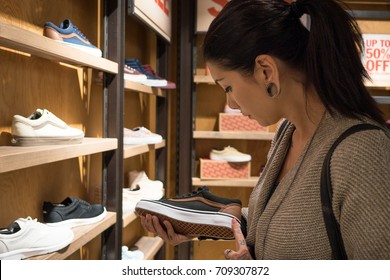 BERLIN, GERMANY - CIRCA JULY, 2017: Woman looking at Vans shoes inside store. Vans is an American clothing manufacturer. The brand is available in more than 170 countries worldwide.