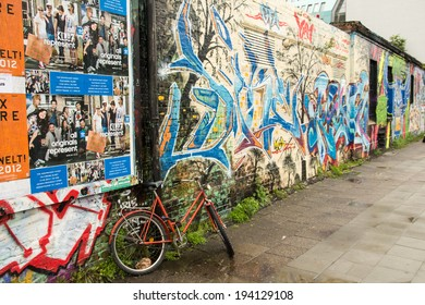 BERLIN / GERMANY - CIRCA SEPTEMBER 2012 - A bicycle is tied against a pole next to a wall filled with graffiti.