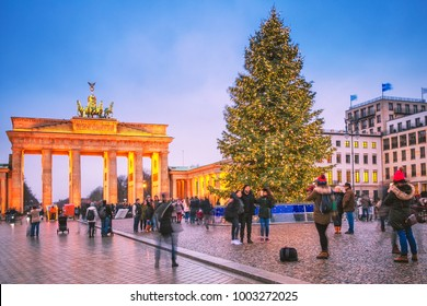 Berlin, Germany.  Classic view of Christmas tree at background of famous Brandenburger Tor (Brandenburg Gate), one of the best-known landmarks and national symbols of Germany, in twilight.