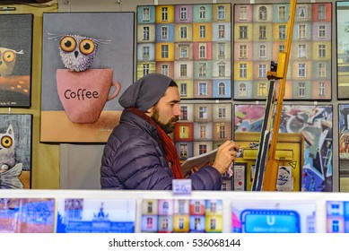 Berlin, Germany - December 02, 2016: The artist paints a picture of a street at the Christmas fair in Germany.