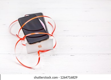 BERLIN, GERMANY - DECEMBER 09, 2018: latest Apple iPhone XS smartphone box and ribbon red heart against white wooden background. Valentine day present concept with copy space