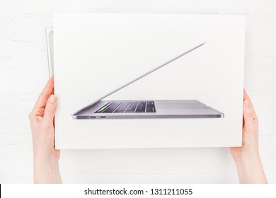 BERLIN, GERMANY - DECEMBER 09, 2018: Woman hands holding the box of the latest Apple Macbook Pro laptop computer against white wooden background. Unboxing top view concept with copy space