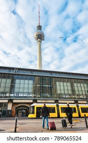 Berlin, Germany - December 10, 2017: Passengers with luggage bags on Alexanderplatz and Television tower on the background in Berlin, Germany