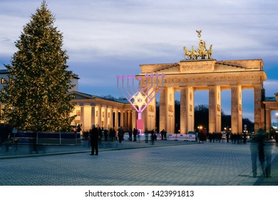 Berlin, Germany - December 13, 2017: People at Hanukkah Menorah and Christmas Tree at Brandenburg gate on Parizer Platz Street in German City centre. Tourists at Brandenburger tor in the evening