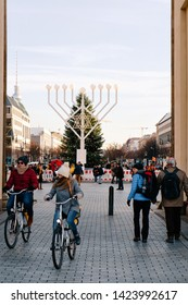 Berlin, Germany - December 13, 2017: People on bicycles at Hanukkah Menorah and Christmas Tree at Brandenburg gate on Parizer Platz Street in German City centre. Tourists at Brandenburger tor