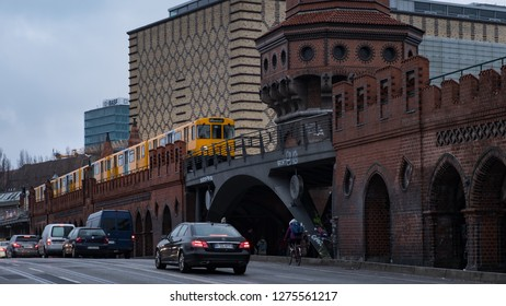 Berlin, Germany -  December 15, 2018 : A yellow electric train passing over Oberbaum Bridge with cars driving on road in Berlin City.