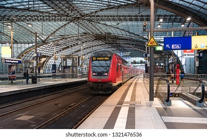 Berlin, Germany - December 15, 2018 : A red train arriving at Berlin Hauptbahnhof Central Station, the main railway station in Berlin.