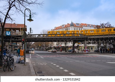 Berlin, Germany - December 15, 2018 : A yellow electric train passing over metal bridge at Schlesisches Tor, Berlin U-Bahn station.