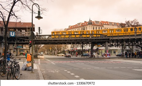 Berlin, Germany - December 15, 2018 : A yellow electric train passing over metal bridge at Schlesisches Tor, Berlin U-Bahn station in beautiful golden light.