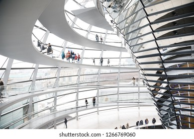 BERLIN, GERMANY - DECEMBER 16, 2018: Visitors inside the glass dome on the top of Reichstag Building, a seat of the German Parliament (Deutscher Bundestag) and popular tourist attraction