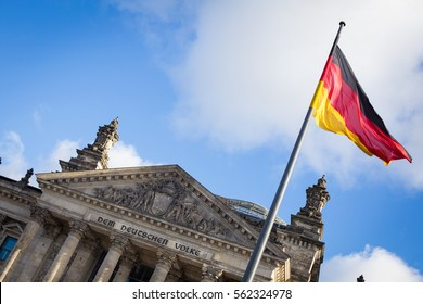 Berlin, Germany, December 2, 2016. German national flag in front of the famous Reichstag building.