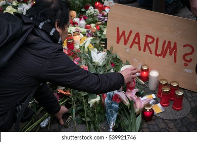 Berlin, Germany - december 20, 2016: Man put candle  and flowers at the Christmas Market in Berlin, the day after the terrorists attacked with a truck