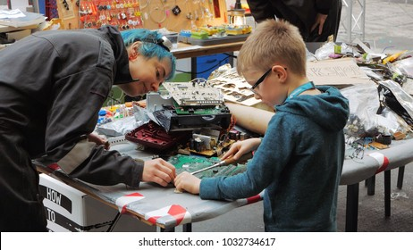 Berlin, Germany, December 2017: Young boy disassembles computer motherboard at a public Maker space event in Berlin.