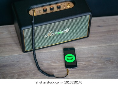 BERLIN, GERMANY - December 3.,2017.: Marshall amp linked by bluetooth to smartphone. Spotify mobile application on smartphone.