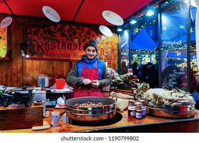 Berlin, Germany - December 8, 2017: Man selling chestnuts at Christmas Market at Gendarmenmarkt in Winter Berlin, Germany. Advent Fair Decoration and Stalls with Crafts Items on the Bazaar.
