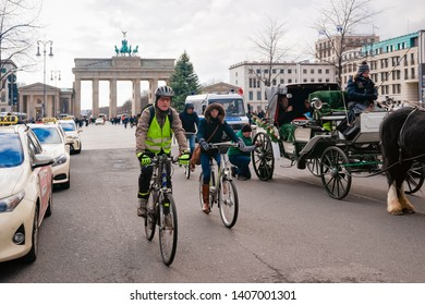Berlin, Germany - December 8, 2017: People on bicycle at Brandenburg gate in Berlin in Germany in Europe in winter. Brandenburger Tor, panorama of German European city wall. With Christmas tree