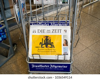 BERLIN, GERMANY - FEB 8, 2018: Man holding buying Die Zeit German politic news paper at press kiosk in Berlin about the stability of German politics