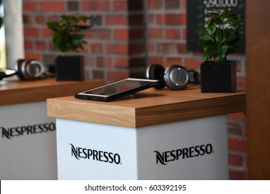 Berlin, Germany - February 17, 2017: digital tablet computer and music headset in Nespresso shop. Nespresso machines brew espresso and coffee from coffee capsules, or pods in bar machines