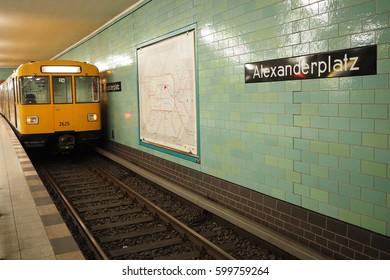 Berlin, Germany- February  28,2017: Yellow underground train (U-Bahn) at train station Alexanderplatz. Alexanderplatz sign visible on the wall